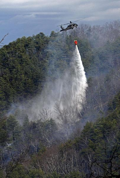 A Blackhawk helicopter from the Tennessee Air National Guard dumps hundreds of gallons of water on the mountains at the Black Bear Ridge Resort, where a fire destroyed or damaged 65 structures and charred 165 acres by noon on Monday, March 18, 2013 between Pigeon Forge and the Wears Valley area of Sevier County, Tenn. The fire was reported on Sunday afternoon. (AP Photo/Wade Payne)