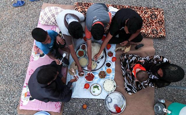 <p>A family breaks their fast on the first day of the Muslim holy month of Ramadan, at al-Khazir camp for the internally displaced, located between Arbil and Mosul, on May 27, 2017. (Photo: Karim Sahib/AFP/Getty Images) </p>