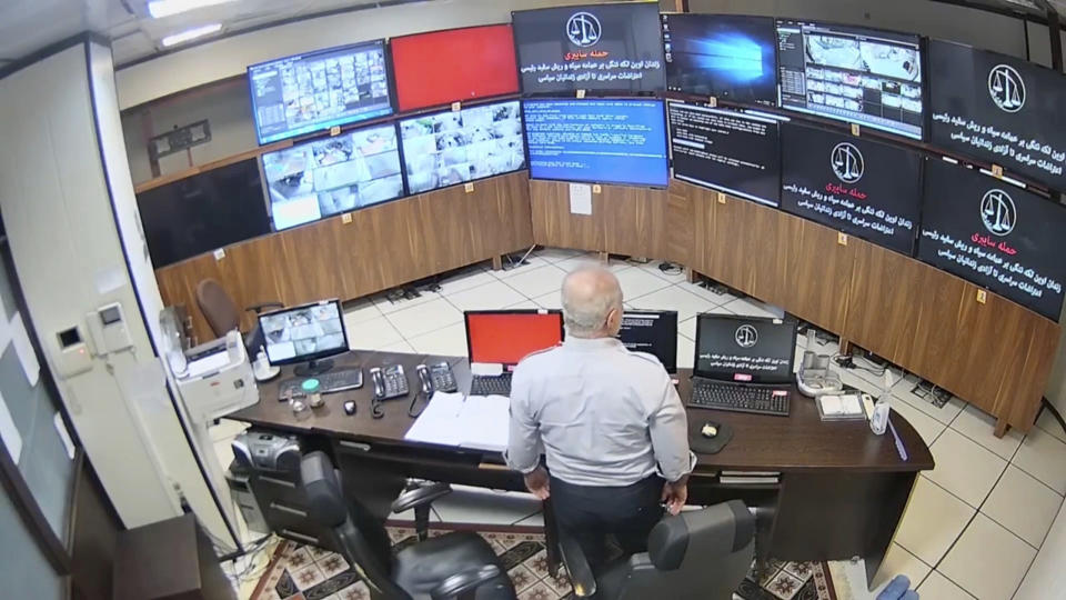 """In this undated frame grab taken from video shared with The Associated Press by a self-identified hacker group called """"The Justice of Ali,"""" a guard looks at surveillance screens taken over by the group, at Evin prison in Tehran, Iran. The alleged hackers said the release of the footage was an effort to show the grim conditions at the prison, known for holding political prisoners and those with ties abroad who are often used as bargaining chips in negotiations with the West. The caption on the screens reads in Farsi: """"Cyberattack: Evin prison is a stain on (Iranian President Ebrahim) Raisi's black turban and white beard. General protest until the freedom of political prisoners."""" (The Justice of Ali via AP)"""