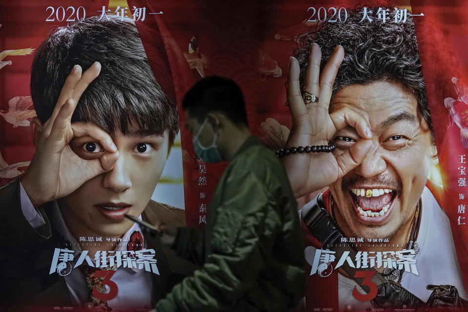 A man wearing a face mask to help curb the spread of the coronavirus walks by a movie poster at Poly Cinema in Beijing on Thursday, Feb. 25, 2021. With coronavirus well under control in China and cinemas running at half capacity, moviegoers are smashing China's box office records, setting a new high mark for ticket sales in February, with domestic productions far outpacing their Hollywood competitors. (AP Photo/Andy Wong)