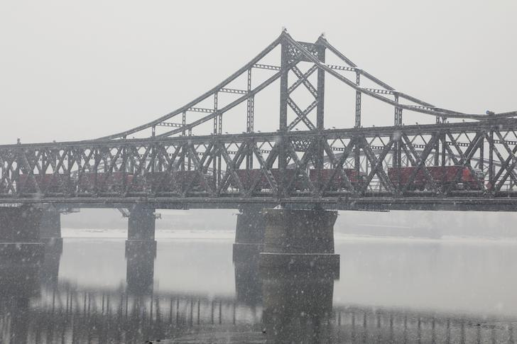 Trucks cross the Friendship Bridge on the Yalu river from Sinuiju, North Korea to Dandong