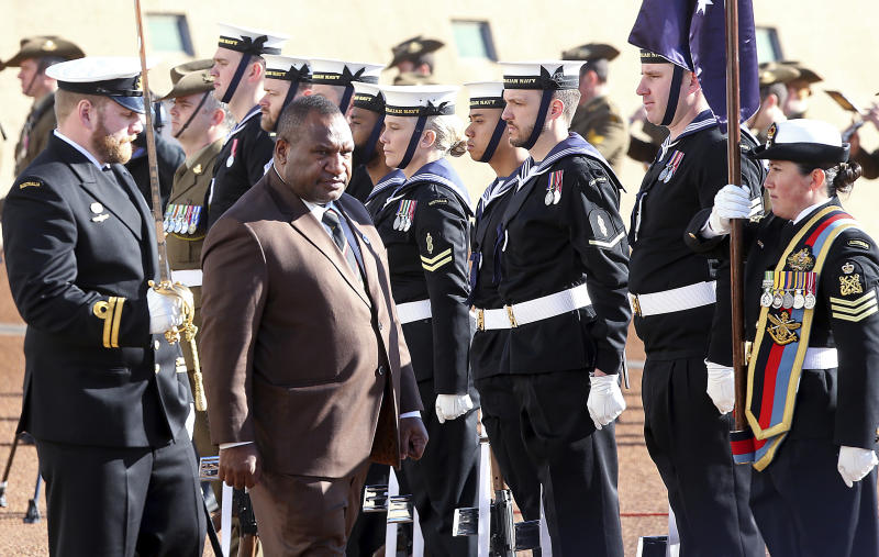 Papua New Guinea Prime Minister James Marape, second from left, inspects troops as he is officially welcomed to Australia's Parliament House in Canberra Monday, July 22, 2019. Marape says his country's relationship with China in not open to discussion during his current visit to Australia. (AP Photograph/Rod McGuirk)