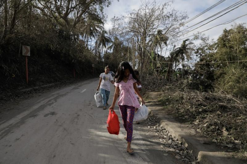 A family walks with bags of belongings as they flee from their town following Taal Volcano's eruption,