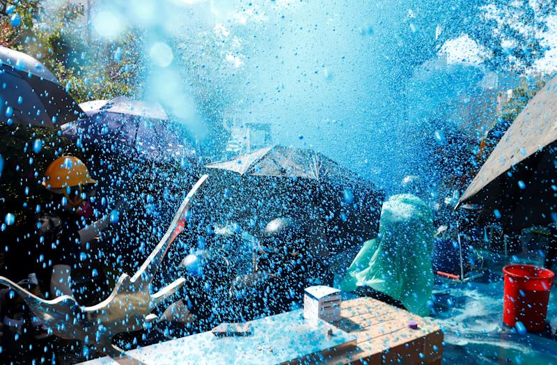 Protesters are sprayed with blue liquid from water cannon during clashes with police outside Hong Kong Polytechnic University (PolyU) in Hong Kong, China Nov. 17, 2019. (Photo: Thomas Peter/Reuters)