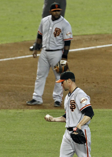 FILE - In this Sept. 16, 2012, file photo, San Francisco Giants' Ryan Vogelsong, bottom, looks down at the baseball after giving up a three-run triple to Arizona Diamondbacks' Patrick Corbin as Giants' Pablo Sandoval looks on in the fourth inning during a baseball game in Phoenix. Vogelsong has a little running joke that he is going to plunk Sandoval in the World Baseball Classic to keep the Panda from a three-homer game like the one he produced in Game 1 of the World Series last fall. Sandoval plans to play nice once he pulls on the Venezuela uniform. (AP Photo/Ross D. Franklin, File)