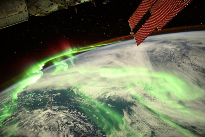 green aurora snaking over earth with space station solar panels in foreground