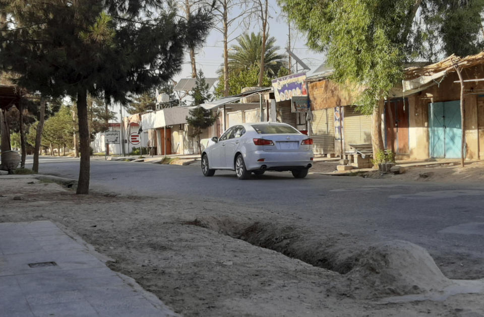 A lone car drives in a deserted street lined with shuttered shops during fighting between Taliban and Afghan security forces, in Lashkar Gah, Helmand province, southern Afghanistan, Tuesday, Aug. 3, 2021. U.S. and Afghan airstrikes were hitting Taliban targets in southern Helmand province on Wednesday, officials said, in an effort to dislodge the insurgents a day after they captured much of the provincial capital of Lashkar Gah. (AP Photo/Abdul Khaliq)