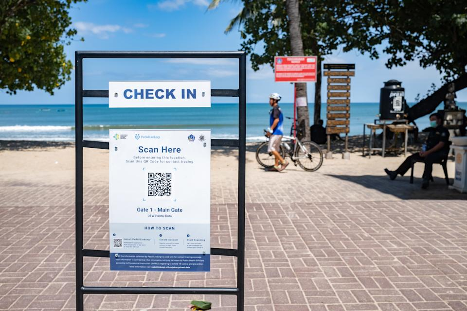 A sign recommends the use of PeduliLindungi App at the beach entrance in Kuta, Bali. Source: EPA