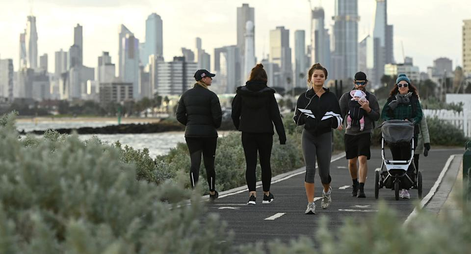 People walk on a path in Melbourne.