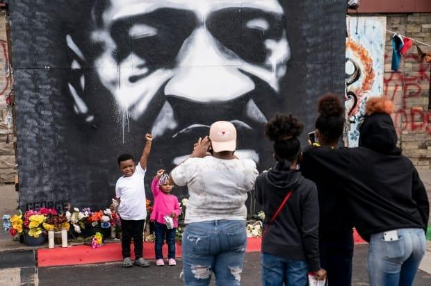 A family takes a photo in front of a mural of Floyd, the 46 year-old Black man whose death nearly a year ago prompted widespread outrage, setting off protests against racism and police brutality across the U.S. and around the world.