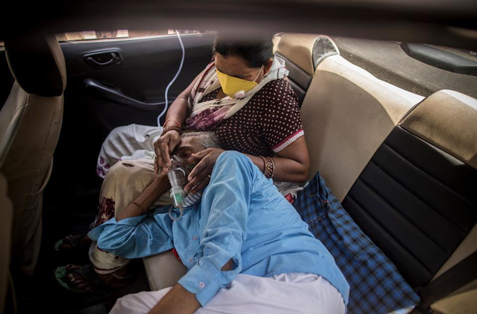 A man can been seen wearing an oxygen mask as a woman with a face mask cradles his head in her lap in the back of car in New Delhi, India.