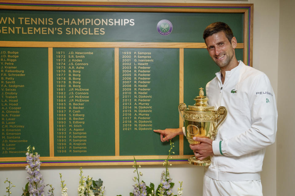 LONDON, ENGLAND - JULY 11: Novak Djokovic of Serbia celebrates with the trophy  in front of the honours board and points to his name after winning his men's Singles Final match against Matteo Berrettini of Italy on Day Thirteen of The Championships - Wimbledon 2021 at All England Lawn Tennis and Croquet Club on July 11, 2021 in London, England. (Photo by AELTC/Thomas Lovelock - Pool/Getty Images)