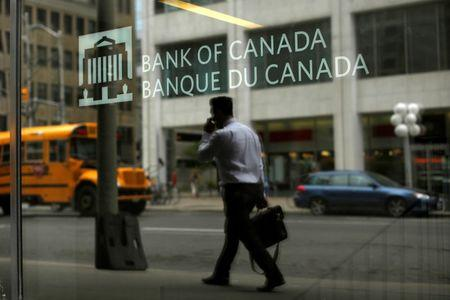 A man is reflected in a window while walking past the Bank of Canada office in Ottawa