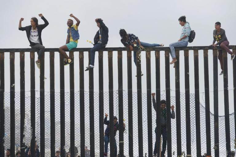 Migrant caravan demonstrators climb the US-Mexico border fence during a rally in San Ysidro, California in April 2018 (AFP Photo/Sandy Huffaker)