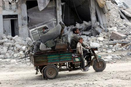 People drive a vehicle through a damaged neighbourhood in the northern Syrian town of al-Bab