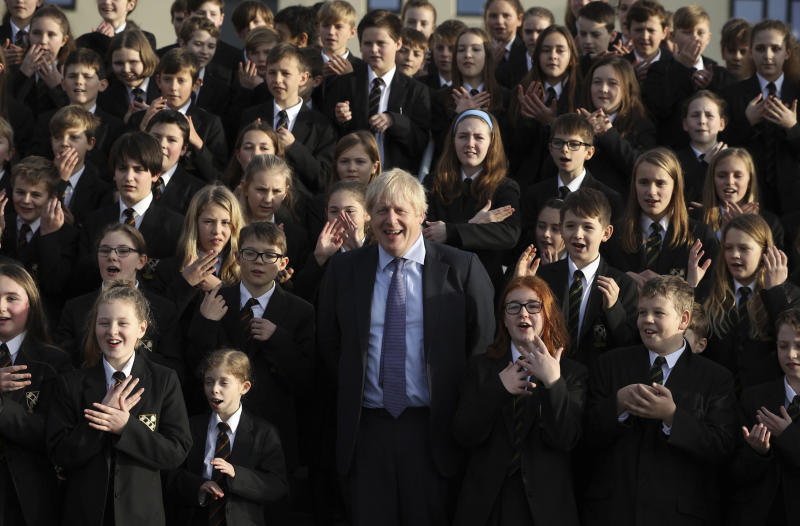 The Chulmleigh College school choir sings and signs 'A Lovely Day' as Britain's Prime Minister and Conservative Party leader, Boris Johnson visit in Chulmleigh, England, Thursday Nov. 28, 2019, ahead of the general election on Dec. 12. (Dan Kitwood/Pool via AP)