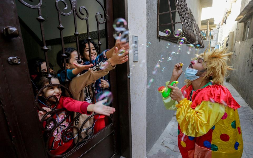 A Palestinian clown wears a protective mask while entertaining children at their home during a lockdown after the outbreak of the coronavirus in Jabalia Refugee Camp in the northern Gaza Strip -  ZUMA Press, Inc. / Alamy Live News