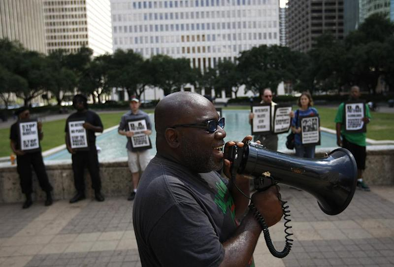 Activist Ali Muhammad with the National Black United Front leads a protest of about 15 people calling for answers from city officials about why a police officer on Saturday fatally shot Brian Claunch, Tuesday, Sept. 25, 2012, outside City Hall in Houston. Claunch, a wheelchair-bound double amputee living in a group home for the mentally ill, was shot and killed by Houston Police in the early morning hours Saturday. Police say HPD officer Matthew Martin shot and killed Claunch, who was waving an object in his hand that turned out to be a pen. (AP Photo/Houston Chronicle, Johnny Hanson)