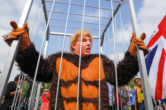 <p>A demonstrator in a gorilla suit and a mask in the likeness of President Donald Trump, stands in a cage in Parliament Square in London, U.K., on Friday, July 13, 2018. (Photo: Luke MacGregor/Bloomberg via Getty Images) </p>