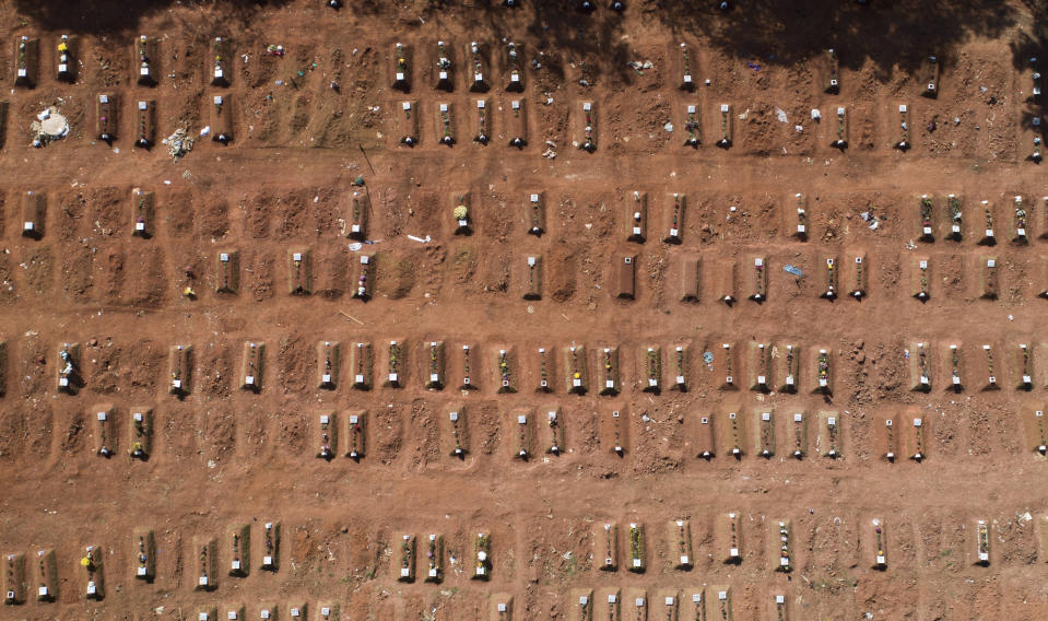 Recently occupied graves cover an area of the Vila Formosa cemetery amid the new coronavirus pandemic in Sao Paulo, Brazil, Thursday, Aug. 6, 2020. Brazil is nearing 3 million cases of COVID-19 and 100,000 deaths. (AP Photo/Andre Penner)