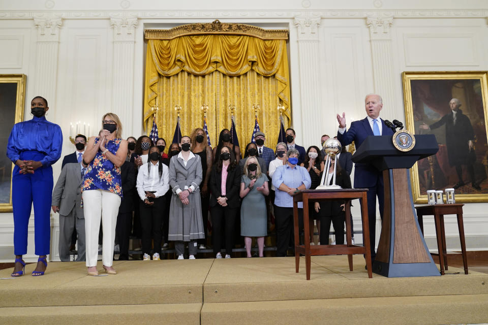 President Joe Biden, right, speaks as he welcomes the Seattle Storm to the East Room of the White House in Washington, Monday, Aug. 23, 2021, for their 2020 WNBA Championship. Going him on stage is Crystal Langhorne, former Seattle Storm player and Director of Community Engagement, Force4Change, left, and Ginny Gilder, Seattle Storm owner, second from left. (AP Photo/Susan Walsh)