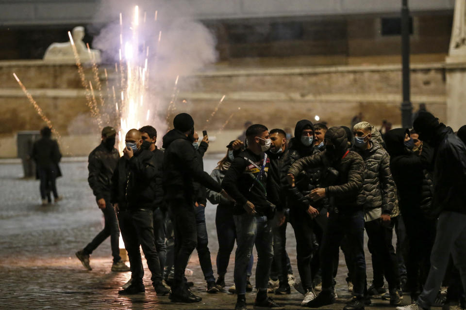 Flares explode as people gather in Piazza del Popolo square during a protest called by Forza Nuova far right group against the government restriction measures to curb the spread of COVID-19, in Rome Saturday, Oct. 24, 2020. A midnight-to-5 a.m. curfew in Italy's Lazio region, which includes Rome, begins on Friday and lasts for 30 days, under orders from regional governor Nicola Zingaretti. (Cecilia Fabiano/LaPresse via AP)