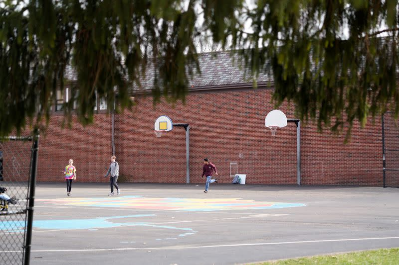 Kids play on a playground at Edwin D. Smith Elementary School ahead of the statewide school closures in Ohio in an effort to curb the spread of the coronavirus