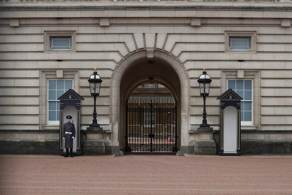A member of the military stands guard outside Buckingham Palace, the official London residence of Britain's Queen Elizabeth II in central London, Sunday, March 7, 2021. The time has finally come for audiences to hear Meghan and Harry describe the backstory and effects of their tumultuous split from royal life, during an interview with U.S. TV host Oprah Winfrey, and British audiences will wake up Monday to headlines and social media posts. (AP Photo/Matt Dunham)