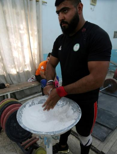 Ali Hamza, a member of the Iraqi national weightlifting team, chalks his hands while exercising during a training session at Badra weightlifting club