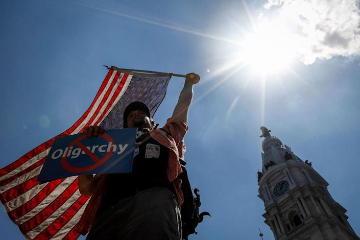 <p>A demonstrator waves an American flag during a rally near City Hall in Philadelphia, Wednesday, July 27, 2016, during the third day of the Democratic National Convention. (Photo: John Minchillo/AP)</p>