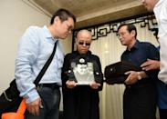 Photo provided by the Shenyang Municipal Information Office shows late Nobel laureate Liu Xiaobo's wife Liu Xia (C) and his brother, Liu Xiaoguang (L), holding a portrait of Liu Xiaobo at a funeral parlour in the city of Shenyang on July 15, 2017