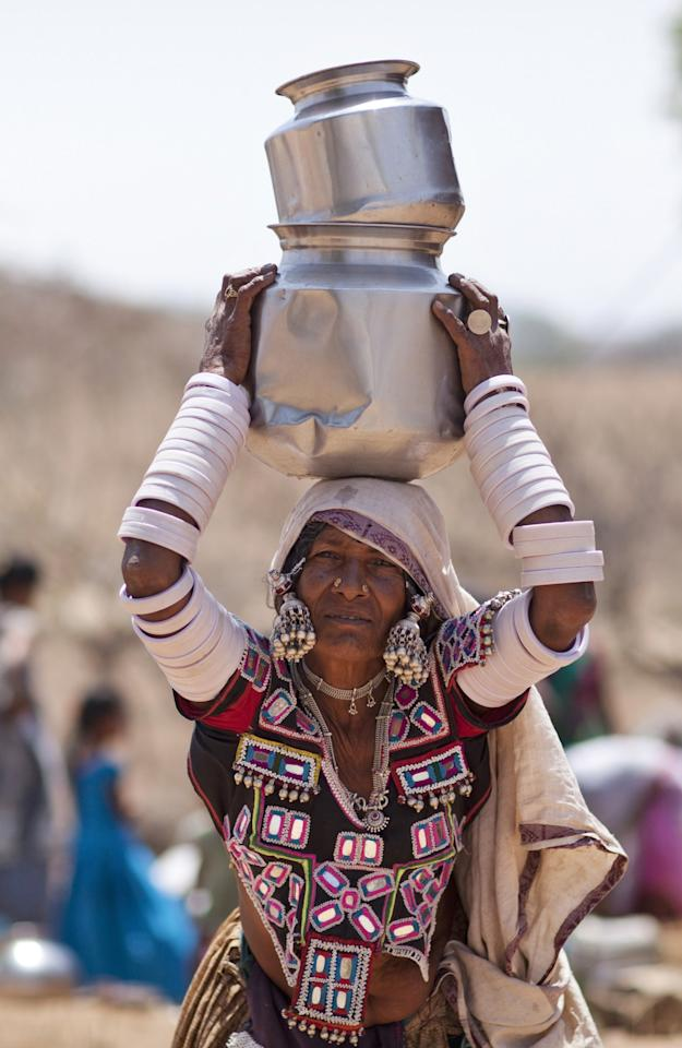 <p>An indigenous Indian woman in her traditional attire walks after collecting water from public tap on the eve of World Water Day, outskirts of Hyderabad, India, Tuesday, March 21, 2017. There is no direct supply of potable water at homes in most of the poor neighborhoods in the country and people have to depend on regulated supply of water from public taps erected on roadsides, with a single tap catering to hundreds of households. (AP Photo/Mahesh Kumar A.) </p>