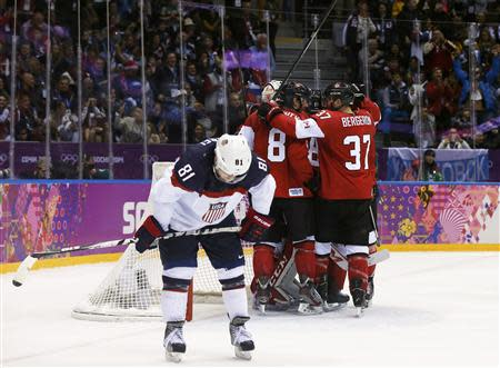 Canada celebrates their men's ice hockey semi-final win as Team USA's Phil Kessel (L) skates away at the Sochi 2014 Winter Olympic Games February 21, 2014. REUTERS/Phil Noble