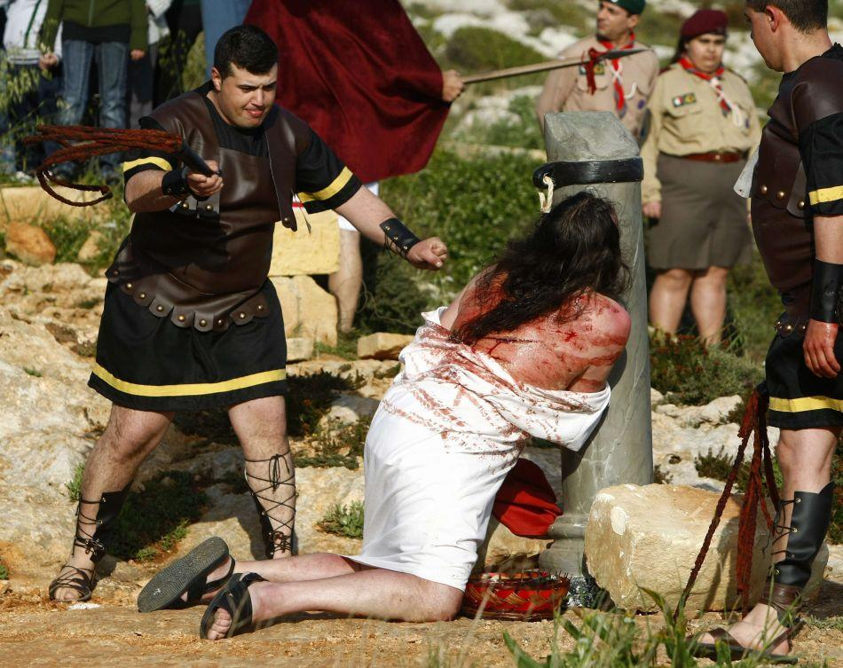Actors take part in a scene of the flogging of Jesus Christ in an interactive street-theatre performance of the Passion of Jesus Christ outside the village of Qrendi, southwest of Valletta, at the start of Easter week March 31, 2012. The Passion play took place between the Neolithic temples of Hagar Qim and Mnajdra, which date back to 3600 BC.