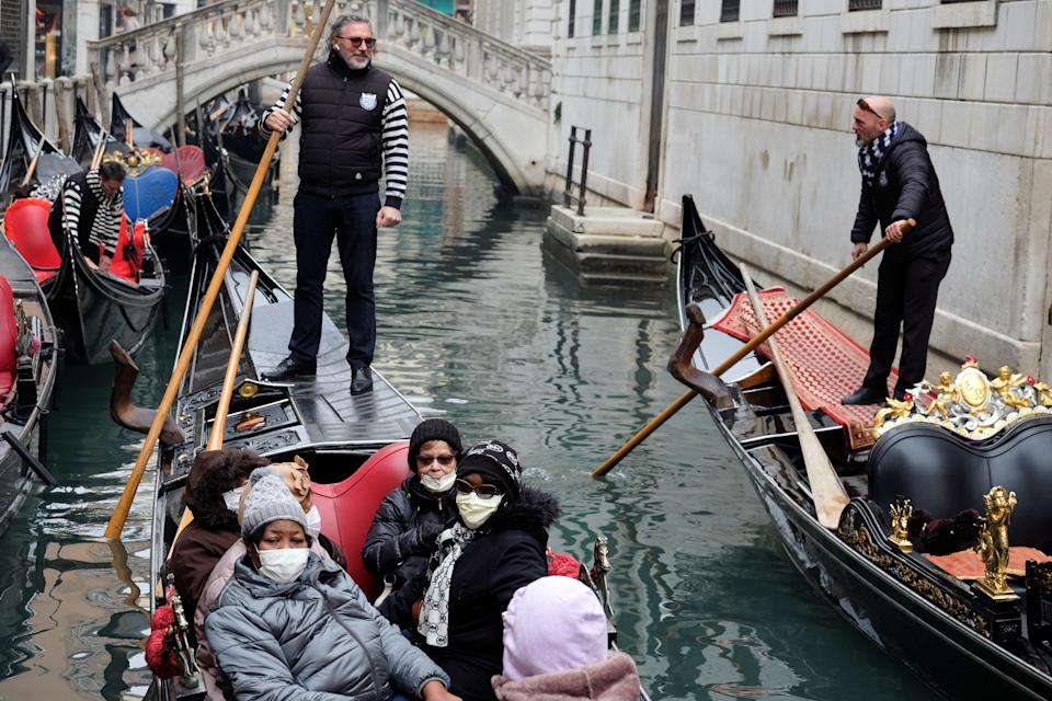 Tourists wear protective face masks on a gondola in Venice because of an outbreak of coronavirus in northern Italy. REUTERS/Manuel Silvestri