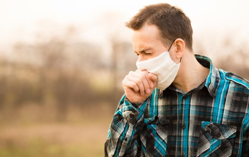 young white man standing outdoors wearing face mask and coughing