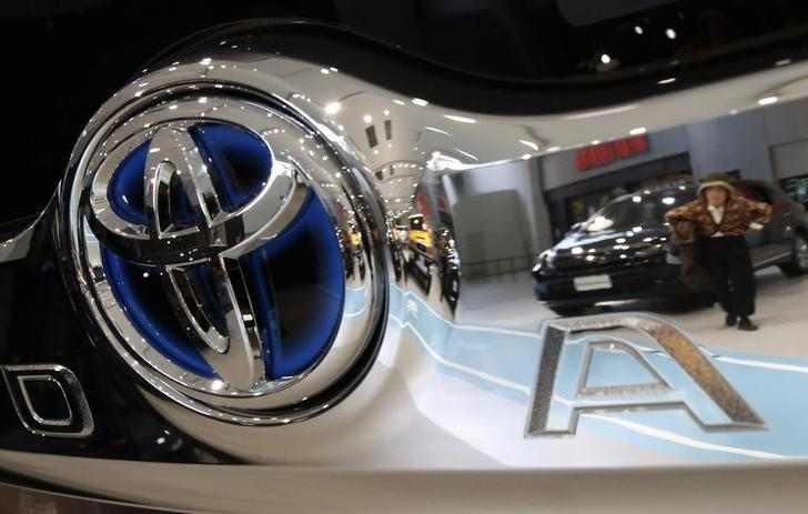 A visitor is reflected in a logo of Toyota Motor Corp at the company's showroom in Tokyo
