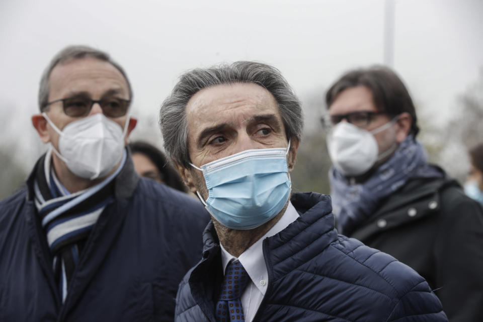 Lombardy region governor Attilio Fontana, center, arrives at a quick coronavirus testing area set up by the Italian Army to ease the pressure on hospital emergency wards, following the surge of COVID-19 case numbers, in Milan, Italy, Friday, Nov. 13, 2020The central government has put under partial lockdown some regions where the rate of virus transmission is particularly high and hospitals are running out of staff or space for patients, including in Lombardy, the northern region where the pandemic first erupted in Italy in February. (AP Photo/Luca Bruno)