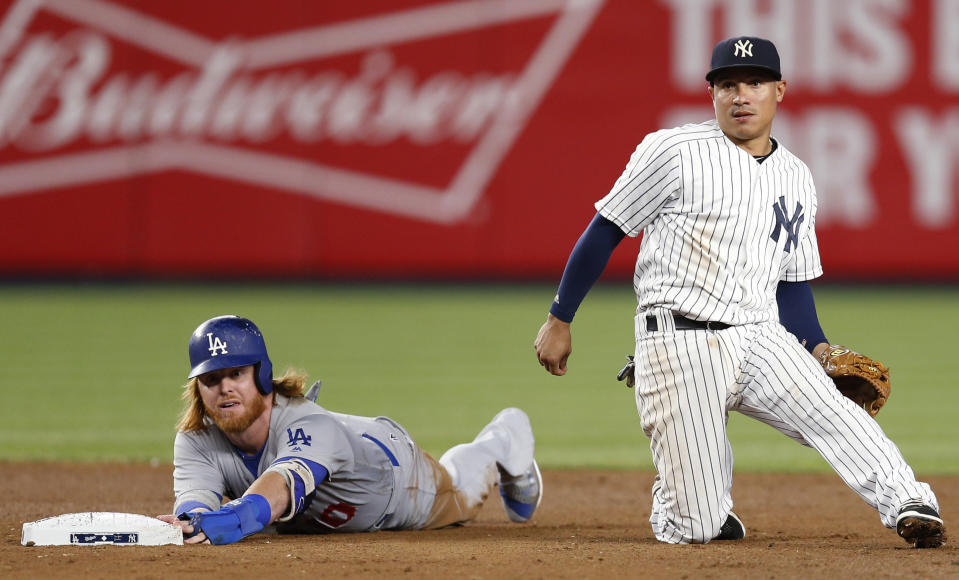 Los Angeles Dodgers' Justin Turner left, and New York Yankees shortstop Ronald Torreyes look toward first after Turner was forced out on a ball hit by Corey Seager, who was safe at first during the sixth inning of a baseball game in New York, Tuesday, Sept. 13, 2016. (AP Photo/Kathy Willens)