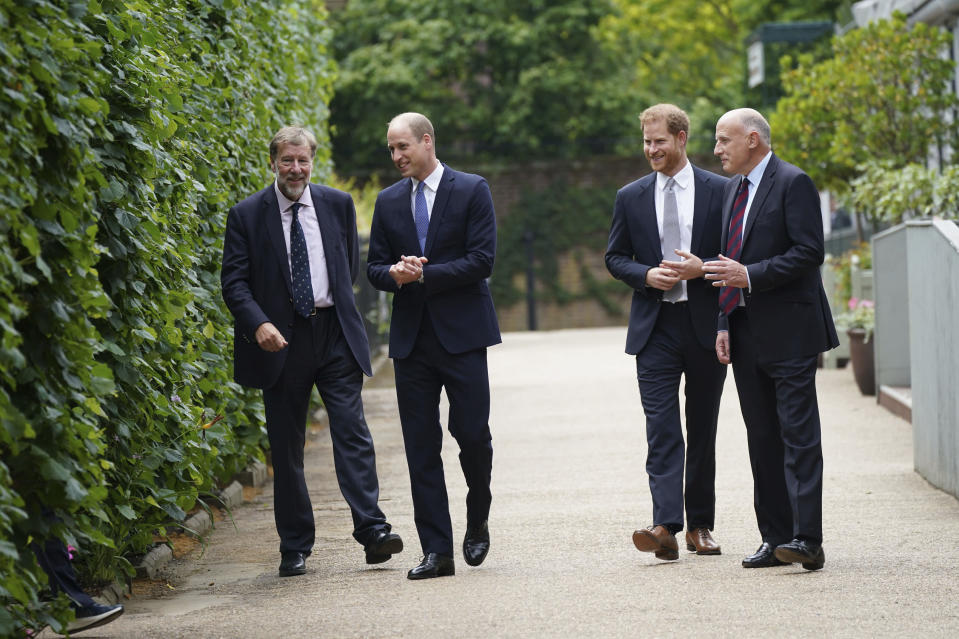 Britain's Prince William, second left, and Prince Harry, second right, talk to, Rupert Gavin, Chairman of Historic Royal Palaces, left, and Jamie Lowther-Pinkerton the former Private Secretary to the Duke and Duchess of Cambridge and to Prince Harry, who sat on the statue committee, ahead of the statue unveiling on what would have been Princess Diana's 60th birthday, in the Sunken Garden at Kensington Palace, London, Thursday July 1, 2021. (Yui Mok/Pool Photo via AP)