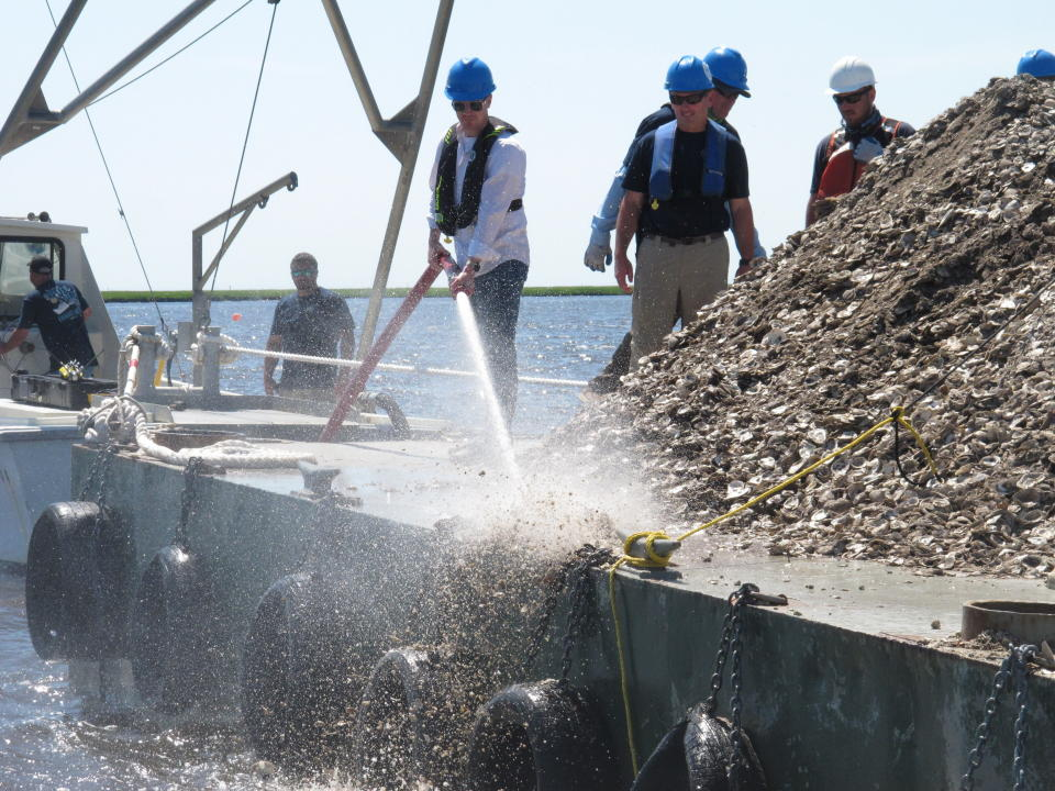 In this June 29, 2021 photo, New Jersey Environental Protection Commissioner Shawn LaTourette, left, uses a high-pressure hose to blast clam and oyster shells from a barge into the Mullica River in Port Republic, N.J. The shells are collected from restaurants in Atlantic City, dried, and placed into the river where they become the foundation for new oyster colonies as free-floating baby oysters attach to them and start to grow. Communities around the world are running similar shell recycling programs. (AP Photo/Wayne Parry)