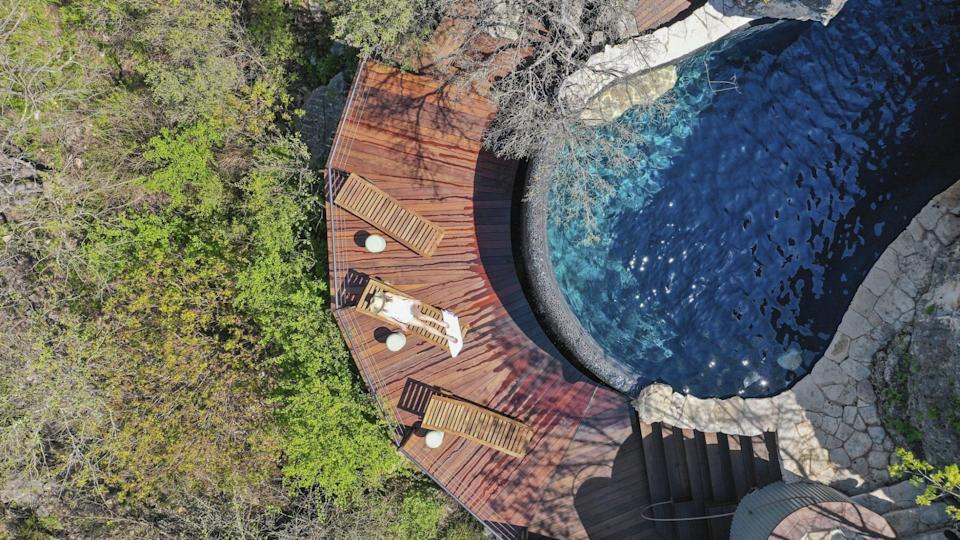 <p>The elegantly designed pool is wrapped in limestone and also features a waterfall. </p>