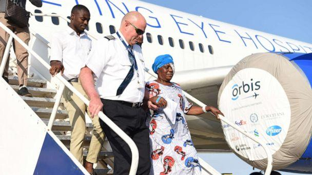 PHOTO: Peter Pitzer departs an Orbis plane in Ghana with a woman treated for a vision problem. (Orbis)