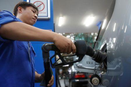 An employee pumps petrol into a car at a petrol station in Hanoi