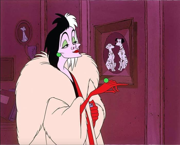 Animated Cruella de Vil looking at a photo of dogs
