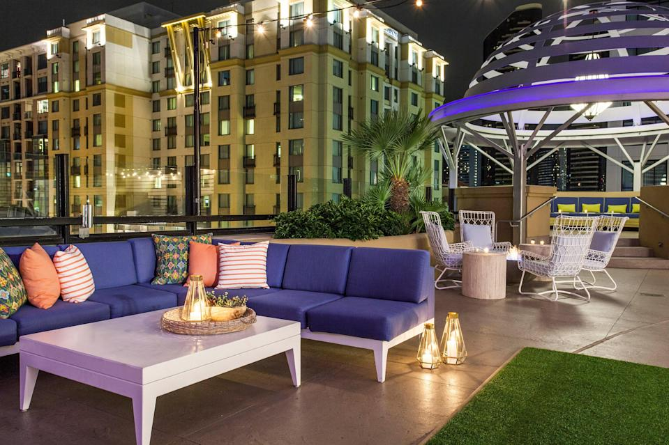 """<p><strong>How did it strike you on arrival?</strong><br> This hotel is located in the East Village, a quickly developing downtown neighborhood with warehouse-style restaurants, hip bars, and baseball at <a href=""""https://www.cntraveler.com/activities/san-diego/petco-park?mbid=synd_yahoo_rss"""" rel=""""nofollow noopener"""" target=""""_blank"""" data-ylk=""""slk:Petco Park"""" class=""""link rapid-noclick-resp"""">Petco Park</a>. Enter through the brick building and you'll find a spacious lobby with warm woods and modern decor. It's trendy but approachable.</p> <p><strong>What's the crowd like?</strong><br> The crowd is a mix. You'll see couples of all ages, families with young children, bachelor and bachelorette parties, and some business travelers.</p> <p><strong>On to the big stuff: Tell us about your room.</strong><br> They're not going for understated here. The decor includes prints, metallics, and pops of purple throughout the spacious, 340-square-foot rooms. The suites feature soaking tubs, outdoor patios, and full living areas.</p> <p><strong>How about the little things, like mini bar, or shower goodies. Any of that worth a mention?</strong><br> Yep, the mini-bar (dubbed an """"honor bar"""") offers wine, beer, alcohol, and snacks like gummy bears, as well as corkscrews ($12), intimacy kits ($15), and lip balm ($8). If you forget a razor, your cell phone charger, or other essentials, call down to the front desk—the hotel has them in stock.</p> <p><strong>Please tell us the bathroom won't let us down.</strong><br> Oh no. Actually, you'll probably want to take a selfie in front of the bathroom's graphic black-and-white wallpaper. If you're staying in the Master Suite, get ready for a regal, spa-like bathing experience with a jet tub. The bath and body products are hotel standard: Atelier Bloem made by MALIN+ GOETZ, set up in dispenser pumps.</p> <p><strong>Maybe the most important topic of all: Wi-Fi. Tell us it's free?</strong><br> Not exactly, but the $25 Daily Facilities Fee (included in t"""
