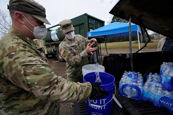 Mississippi Army National Guard Sgt. Chase Toussaint, right, and Staff Sgt. Matthew Riley, both with the Maneuver Area Training Equipment Site of Camp Shelby, fill 5-gallon water drums with non-potable water, Monday, March 1, 2021, at a Jackson, Miss., water distribution site on the New Mount Zion Missionary Baptist Church parking lot.