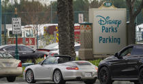 Vehicles queue up outside the Disneyland Resort parking lot for a COVID-19 vaccine in Anaheim, Calif., Wednesday, Jan. 13, 2021. The parking lot is located off Katella Avenue and sits southeast of Disneyland. California is immediately allowing residents 65 and older to get scarce coronavirus vaccines, Gov. Gavin Newsom announced Wednesday. (AP Photo/Damian Dovarganes)