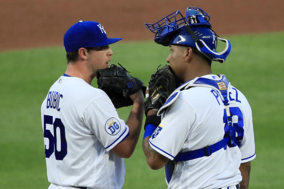Kansas City Royals starting pitcher Kris Bubic (50) and catcher Salvador Perez (13) talks after a run scored during the fourth inning of a baseball game against the Chicago Cubs at Kauffman Stadium in Kansas City, Mo., Wednesday, Aug. 5, 2020. (AP Photo/Orlin Wagner)