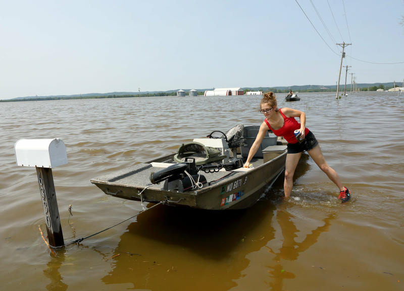 Emily Kientzel puts a cooler in her friend's boat as they prepare to take the boat out over floodwaters from the Mississippi River to his home outside of Portage des Sioux, Mo., Sunday, June 2, 2019. (David Carson/St. Louis Post-Dispatch via AP)